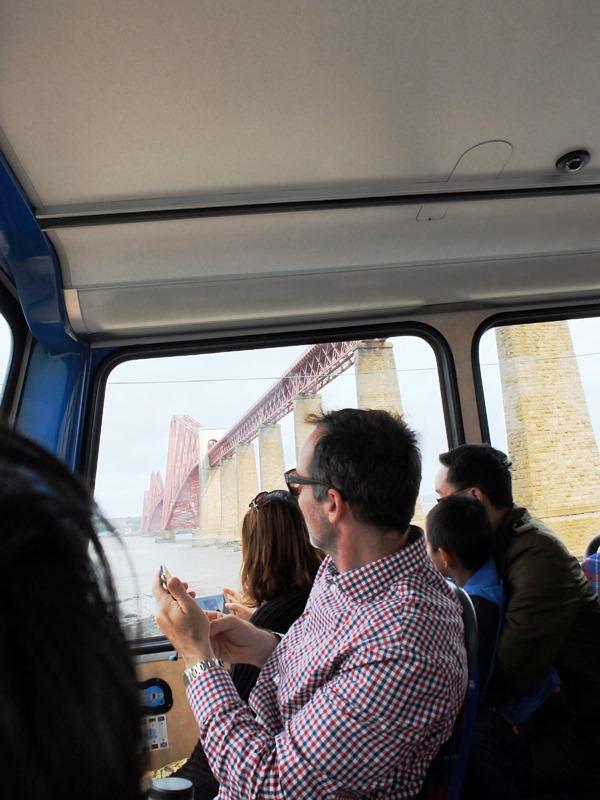 橋を撮影しようと身を乗り出す乗客たち